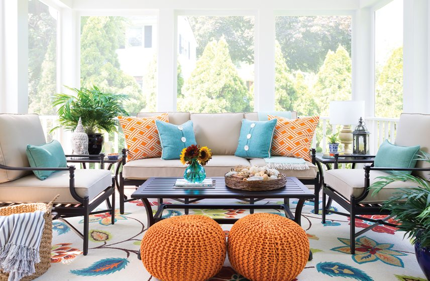 Vibrant orange and aqua enliven the porch, which boasts an outdoor rug by Surya.