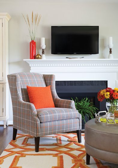 In the living area, a rug in the client's favorite orange hue grounds the space.