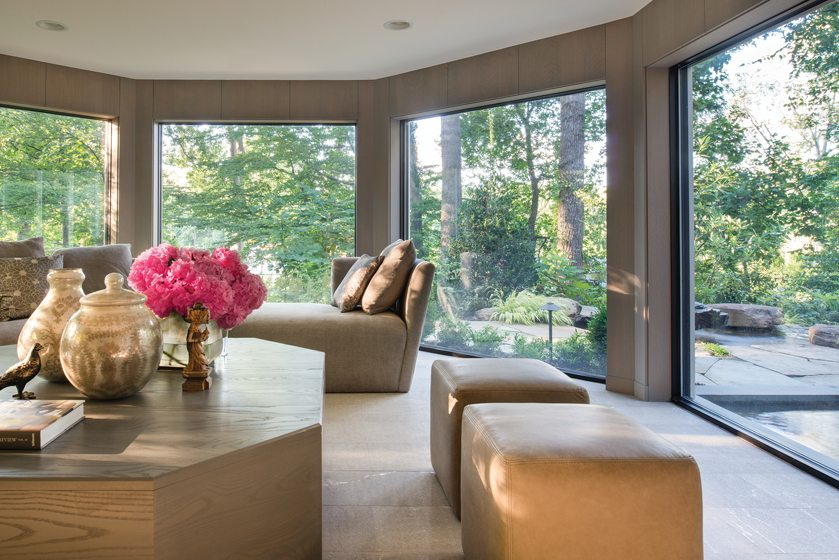 The family room boasts floor-to-ceiling windows and a sectional designed by Drysdale.