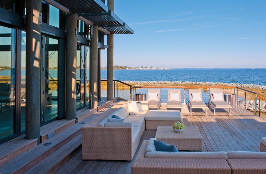 A NanaWall opens to the deck, which features furniture from JANUS et Cie.