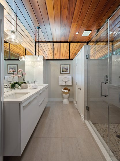 The master bath features a river-stone shower floor and pendants by Niche.