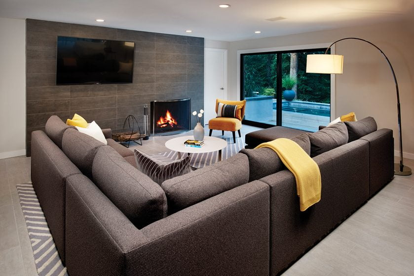 The renovated lower level features a cozy den with a porcelain-tile fireplace wall.
