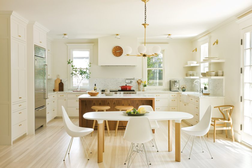 The clean-lined kitchen combines white-painted cabinetry and a walnut island.