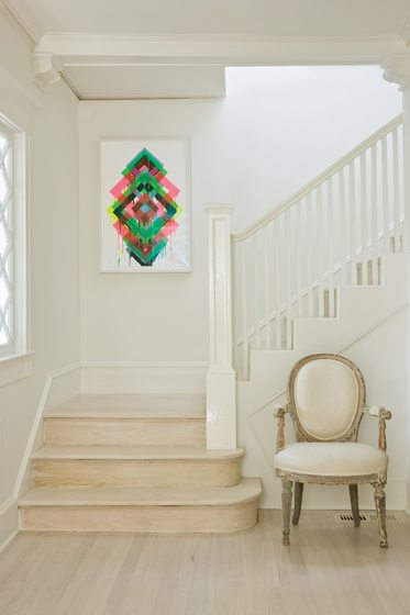 Bleached oak floors and white walls contrast with a bold Maya Hayuk painting.