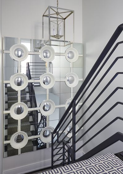 The staircase gets a dash of glam from Global Views' mirrored panels, punctuated by mirrored portholes.