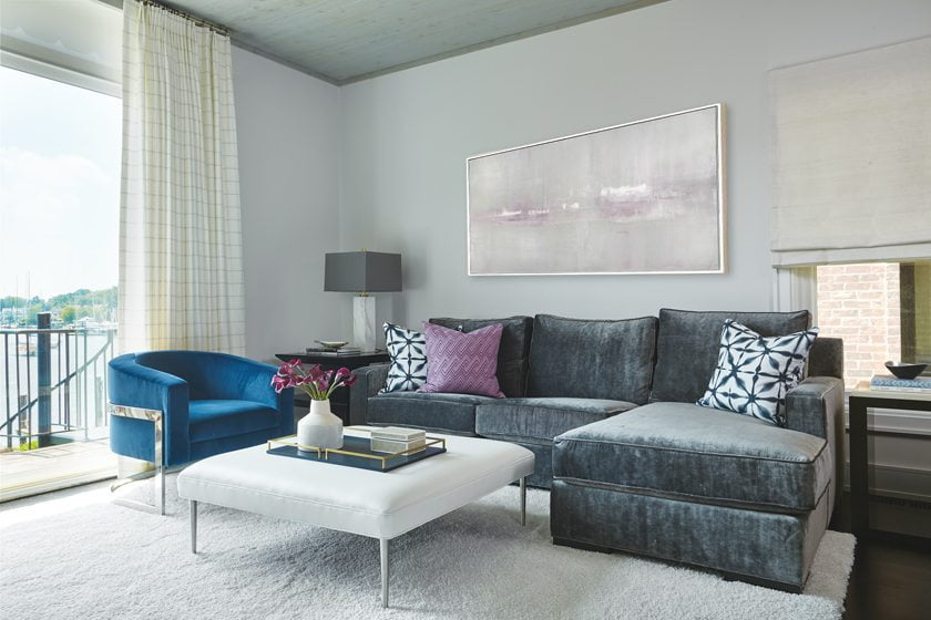 In the living area, a Kravet sectional and a Bernhardt chair surround an AmericanEye ottoman that doubles as a coffee table.