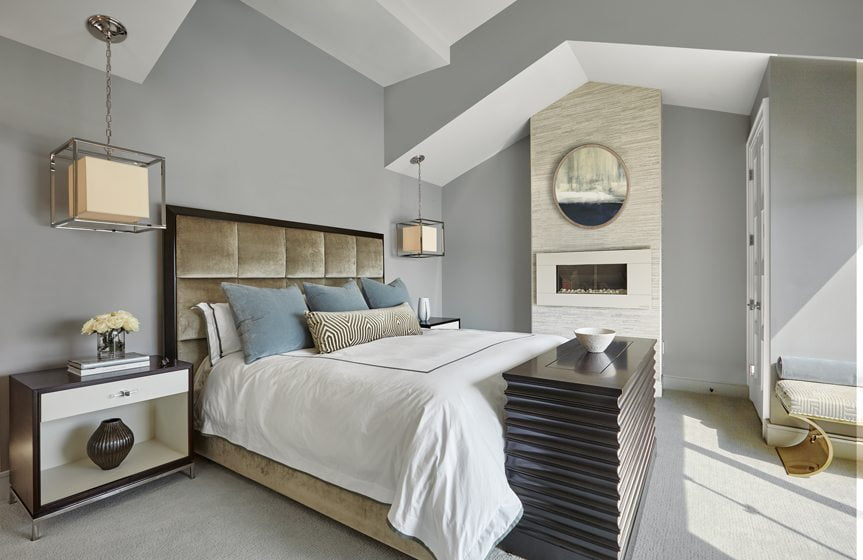 A gas fireplace and bedside pendant lamps from Visual Comfort enhance the master bedroom.