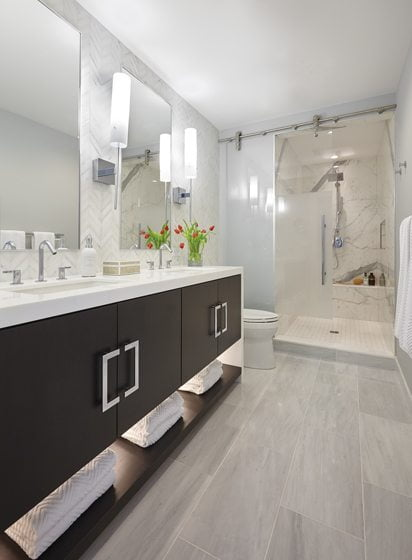 The shower stall in the master bath is lined with large-format faux-marble porcelain sheets called Slim Slabs.