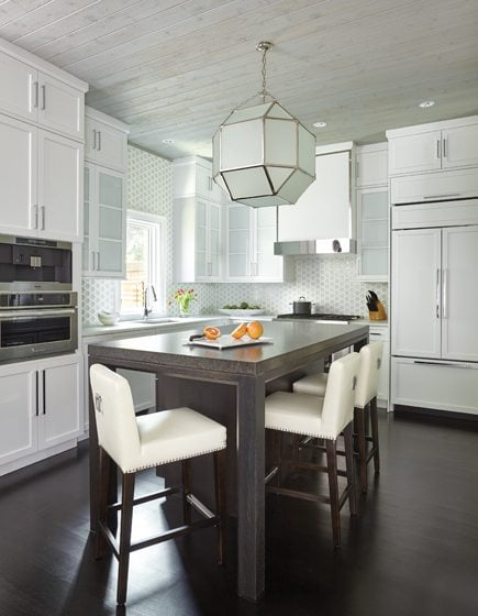 In the crisp, white kitchen, a fixture from Visual Comfort and a glass-tile backsplash from Oceanside Tile add character.