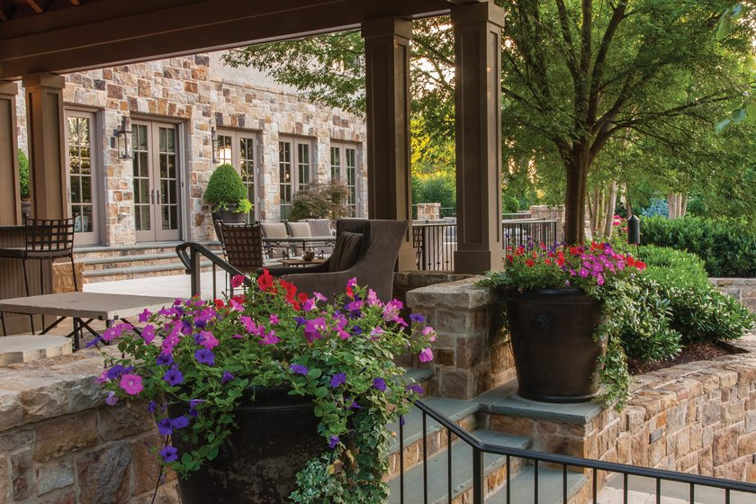 Pots of annuals enliven the upper terrace, which houses a cabana and outdoor dining area.