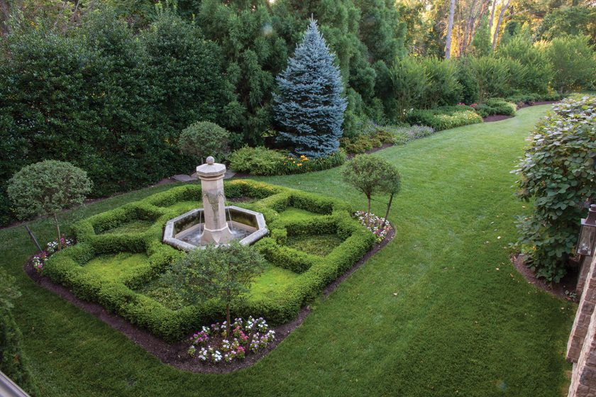 Charles Owen designed a boxwood parterre around an antique fountain.