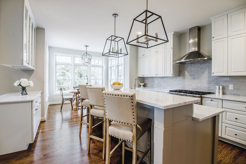 A ceramic-tile backsplash, marble counters and Hinkley pendants adorn the kitchen.