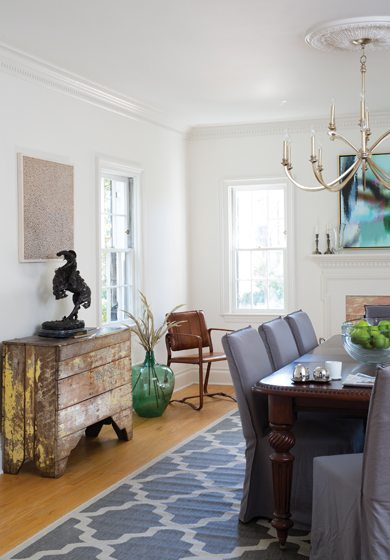 The dining room features a bronze sculpture by artist Frederic Remington displayed on a vintage chest.