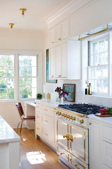 The La Cornue range reflects the white-and-brass color palette.