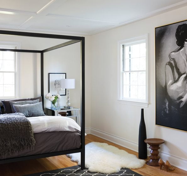 The master bedroom is minimally furnished with a Room & Board canopy bed and mirrored nightstands.