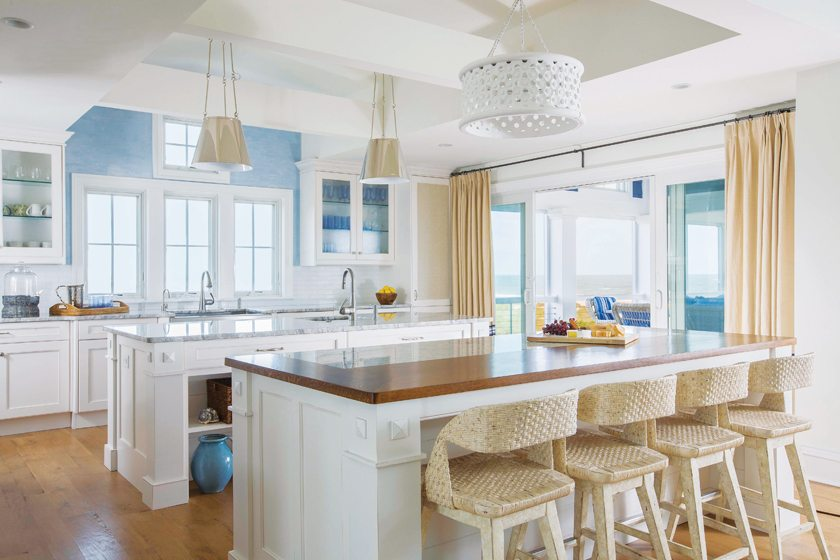 The kitchen islands welcome multiple cooks. The stools are by Stanley and the glass backsplash tile is by Soli.