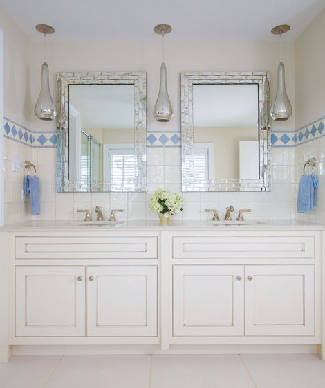 In the master bath, Made Goods mirrors hang between pendants by Arteriors.