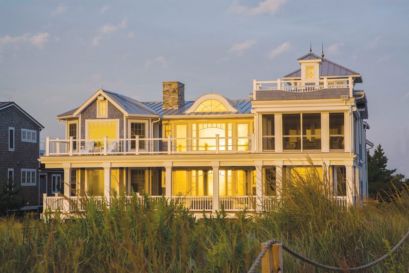 Upper and lower decks and a screened porch overlook the beach.
