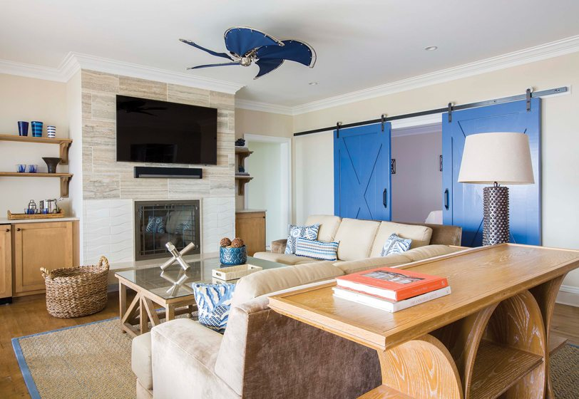 Barn doors by Rustica Hardware separate the family room and movie theater on the first floor.