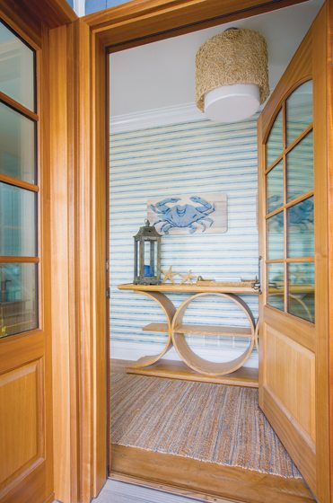 Erin Paige Pitts selected wallpaper in a pale-blue stripe and a Vanguard console for the foyer.