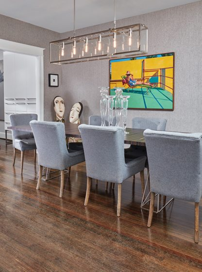 In the dining room, chenille wallpaper from Romo provides a neutral backdrop for a bold painting by Gary Pettigrew.