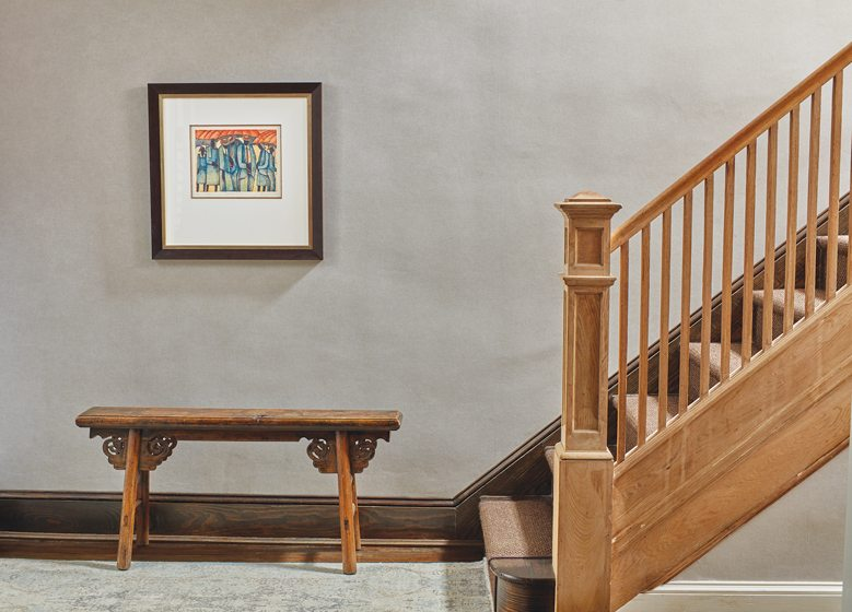 The foyer showcases an antique Chinese elmwood bench beside the original staircase.