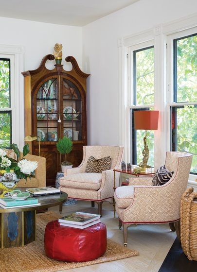 In the great room, Schumacher chairs and a Moroccan pouf gather around a vintage coffee table.
