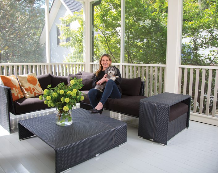 French doors open to the screened porch, where Macklin and her dog Chessy snuggle.