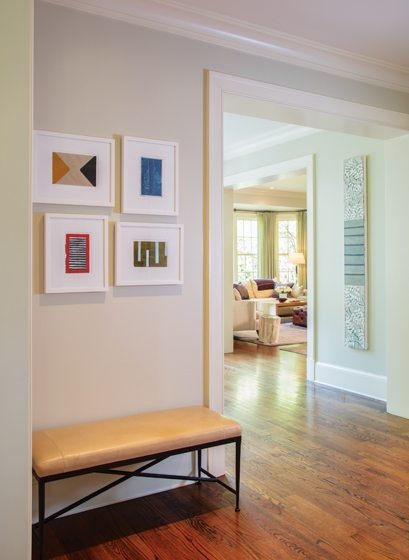 The foyer is simply furnished with a bench and prints discovered at Art Basel in Miami.