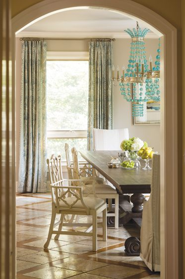 Soft teal accents in Lee Jofa drapes and an Arteriors chandelier enliven the breakfast room.