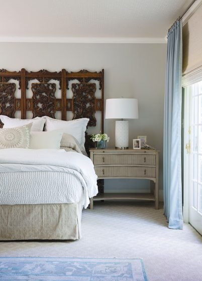 An antique screen serves as a headboard in the master bedroom.
