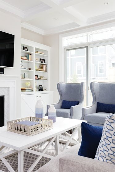 The family room sports Lillian August chairs and a Noir coffee table.