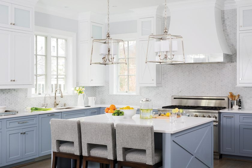 In the kitchen, gray-blue cabinetry is paired with a marble-tile backsplash and a pendant from Visual Comfort.
