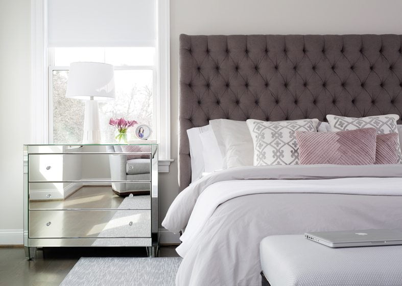 Touches of glam energize the master bedroom, with its mirrored chest of drawers and tufted headboard.