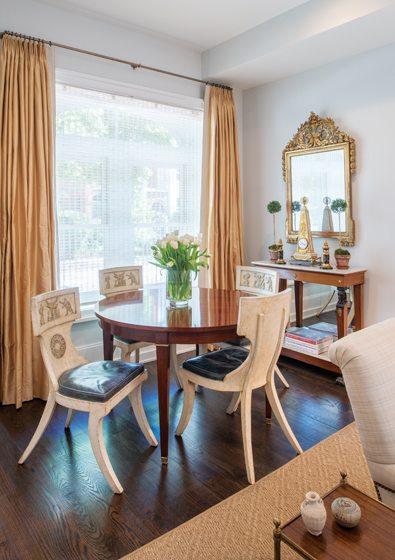 Hampton hosts small dinners around a custom mahogany table rimmed by 19th-century Klismos chairs.