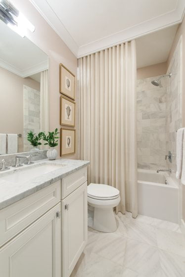 Crown molding and drapery hide the shower in the guest bathroom.