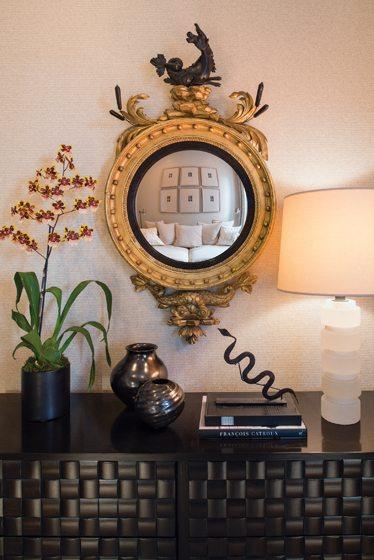 An English Regency convex mirror hangs above a Paul László chest.
