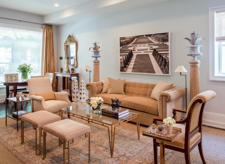 A gilt-bronze Jean Royère-style coffee table and contemporary obelisks with inlaid marble grace the living room.