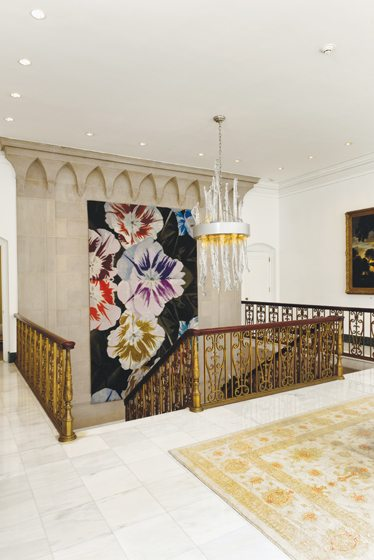 A grand stairway is adorned with a tapestry by Martin van Vreden and a Bernard Heesen chandelier.