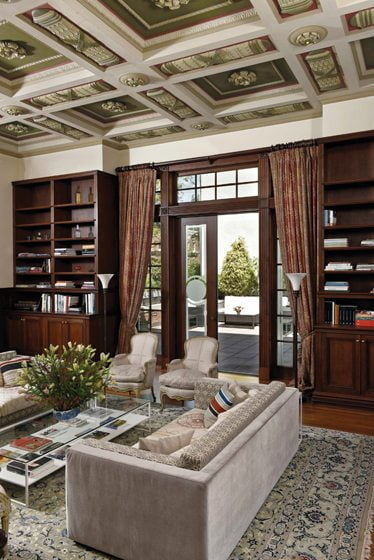 In the library, walnut-and-glass doors lead out to the patio.