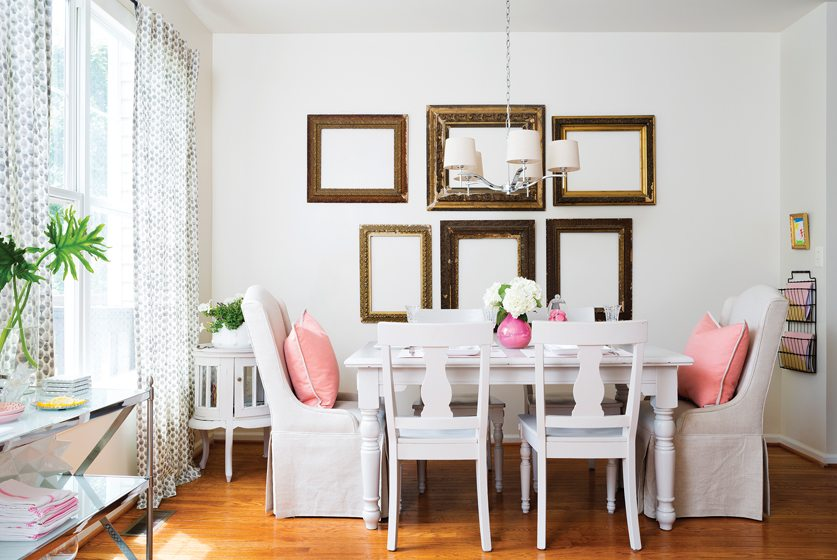 A collection of antique frames in the dining area adds visual interest above a painted table and chairs.