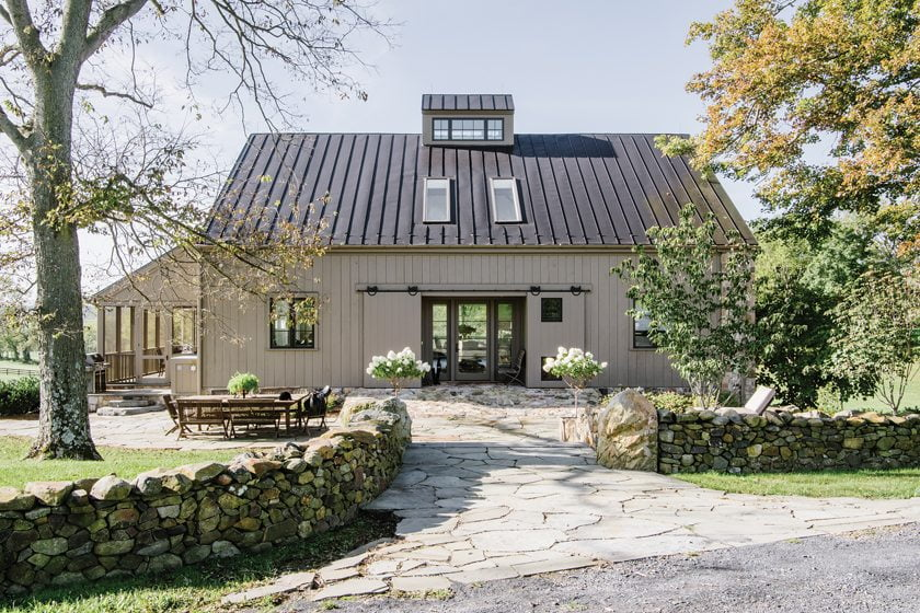 The home's front façade is authentic to the bank-barn style, with sliding barn doors at the entry.