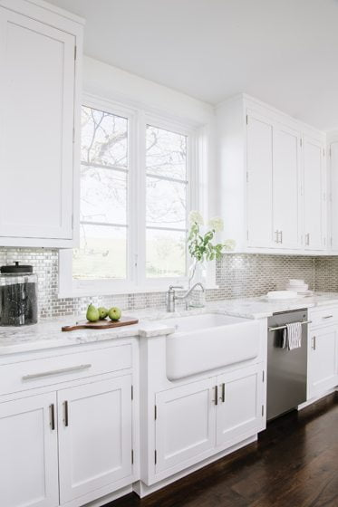 Shaker-style cabinets, marble counters and a farmhouse sink combine with a stainless-steel backsplash.
