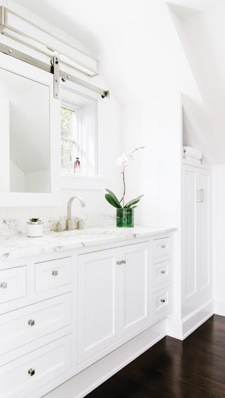The master bathroom combines marble counters and white-paneled cabinetry.