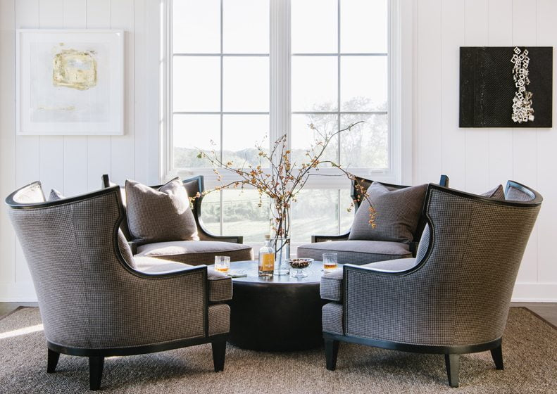 At the far end of the living area, four chairs surround a metal cocktail table by Arteriors.