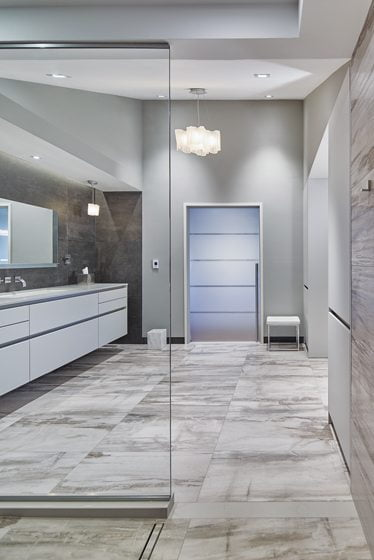 A frosted-glass door with a graphic stripe leads to the private WC.