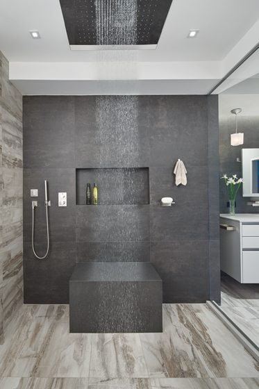 The roomy shower features a built-in seat and a rain shower head.