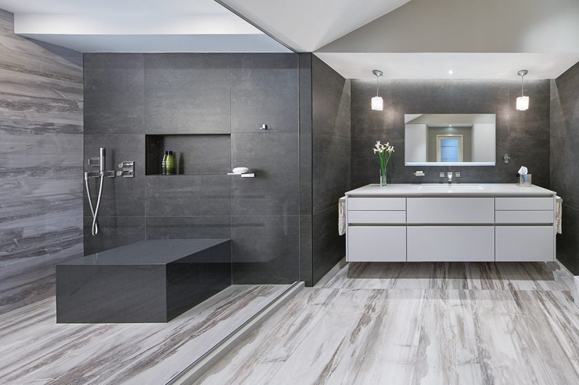 Sleek porcelain-tile surfaces in shades of gray create the backdrop for a stylish master bath with a distinctly masculine edge.