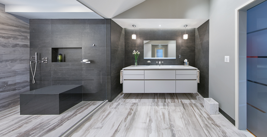 Italian porcelain tile, frosted glass and floating cabinetry topped with Caesarstone convey a sleek sensibility.