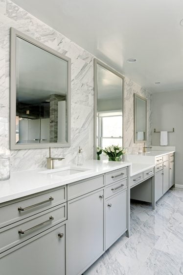 Vanities flank a lowered surface that allows the owner to put on makeup from her chair.